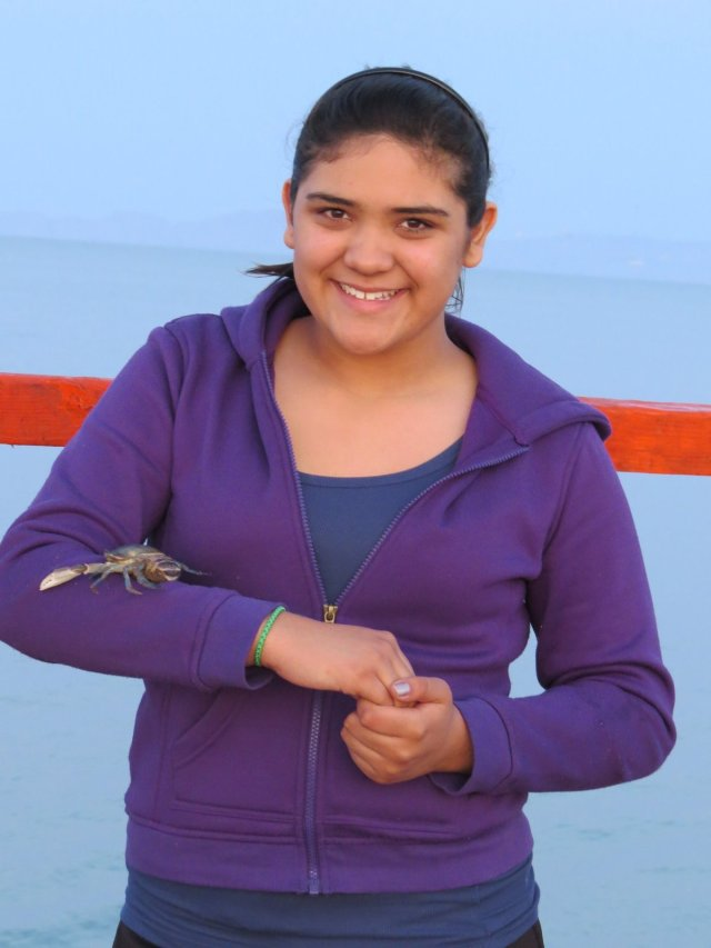 Bravely allowing a crab to walk her arm.