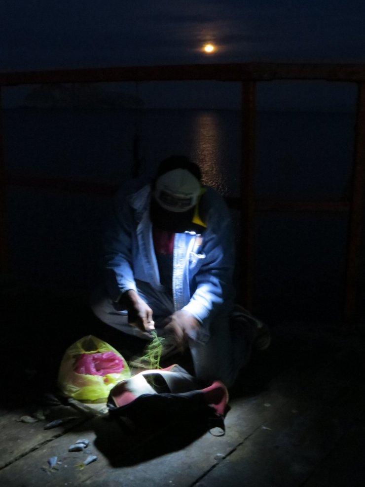 Flashlight tucked under his chin, a fisherman repairs his net.